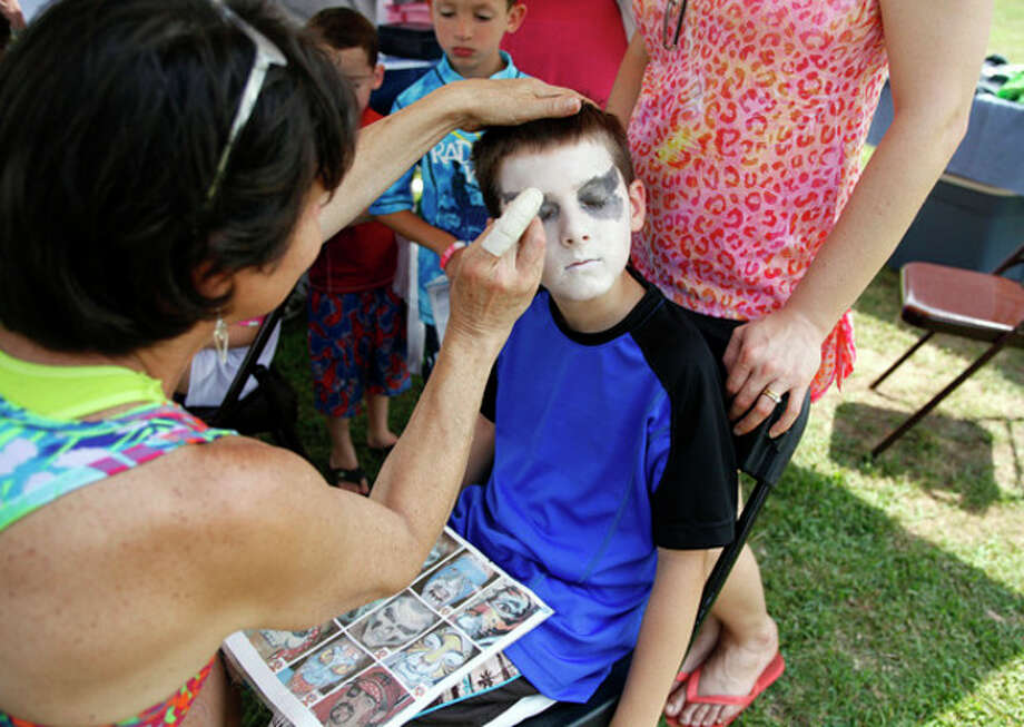 Under the Oyster Festival Tent, Mimi paints the face of Daniel, 9, during the Third Taxing District's Power On The Sound event celebrating their 100th anniversary at Calf Pasture Beach in Norwalk Saturday afternoon.Hour Photo / Danielle Calloway