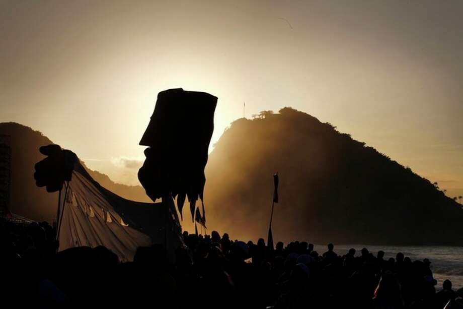 Pilgrims carry a large puppet representing Jesus as the sun raises over Copacabana beach in Rio de Janeiro, Brazil, Sunday, July 28, 2013. Hundreds of thousands of young people slept under chilly skies in the white sand awaiting Pope Francis' final Mass for World (AP Photo/Jorge Saenz) / AP