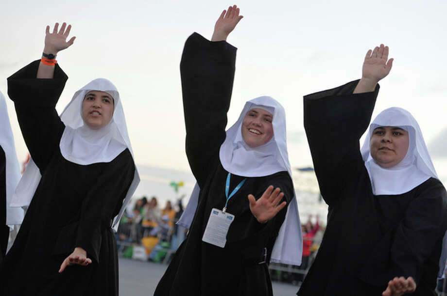 "Nuns dance as they wait for the start of a a vigil on Copacabana beach in Rio de Janeiro, Brazil, Saturday, July 27, 2013. Pope Francis drew faithful to Rio's Copacabana beach on Saturday for the final evening of World Youth Day, hours after he chastised the Brazilian church for failing to stem the ""exodus"" of Catholics to evangelical congregations. (AP Photo/Luca Zennaro, Pool) / ANSA POOL"