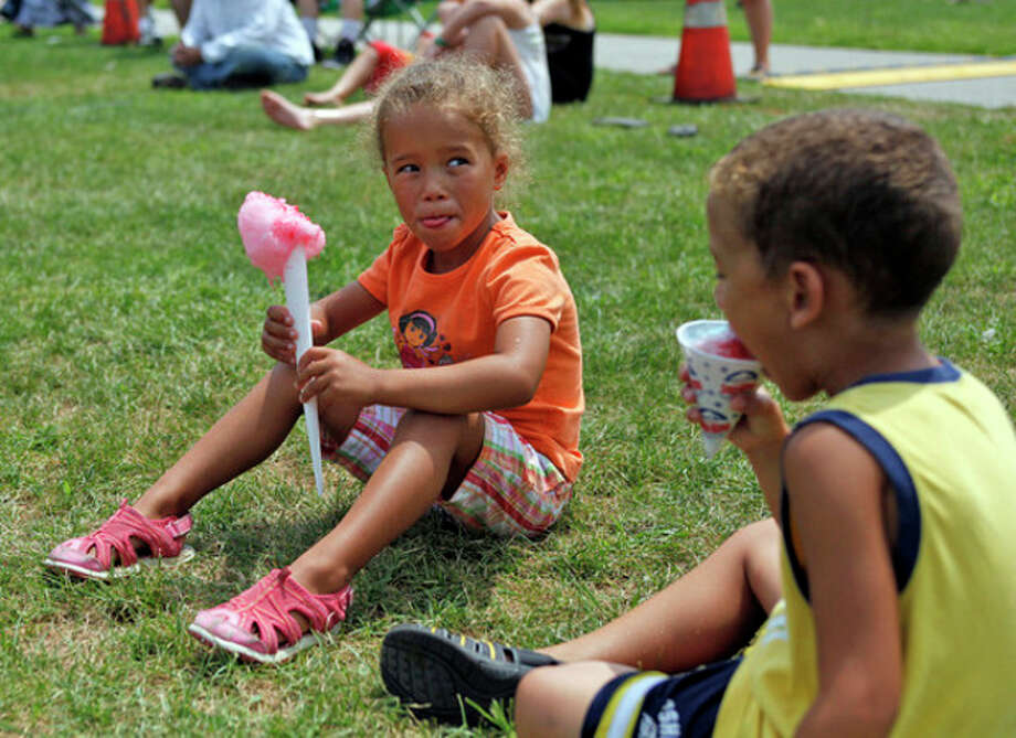 Liana Gomez, 4, and Lucas Gomez, 4, enjoy a sweet treat during the Third Taxing District's Power On The Sound event celebrating their 100th anniversary at Calf Pasture Beach in Norwalk Saturday afternoon.Hour Photo / Danielle Calloway