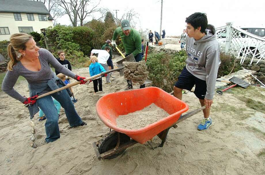 Hour Photo Alex von Kleydorff; Friends Kecia von der ahe and Josh Prince shovel beach sand into a wheelbarrow held by Cameron Haber as clean up continues at the Hood household in Westport.
