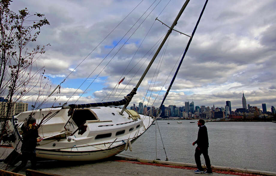 The Manhattan skyline is the backdrop for a sailboat tossed onto the shore in Hoboken, N.J. Wednesday, Oct. 31, 2012 in the wake of superstorm Sandy. Parts of Hoboken are still covered in standing water. Sandy, the storm that made landfall Monday, caused multiple fatalities, halted mass transit and cut power to more than 6 million homes and businesses. (AP Photo/Craig Ruttle) / FR61802 AP