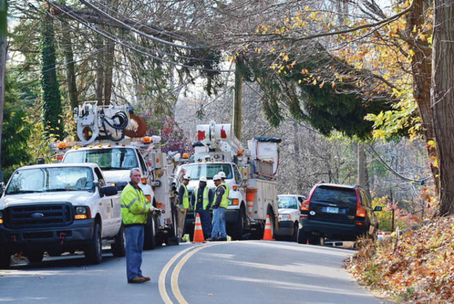 Hour photo / Erik TrautmannOut-of-state line crews wait for tree to be removed before attempting to restore power in Westport. / (C)2012, The Hour Newspapers, all rights reserved
