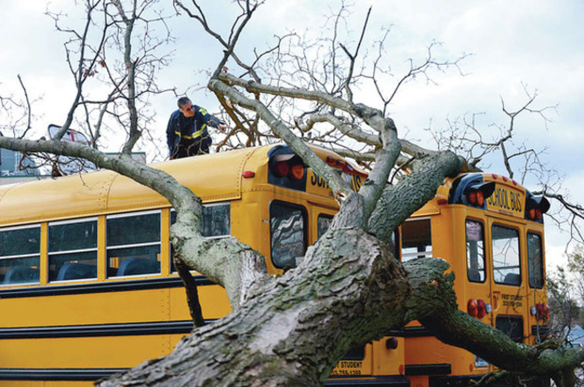 Hour photo / Erik Trautmann First Student Bus Co. employees inspect school buses damaged in the storm at Norwalk High School.