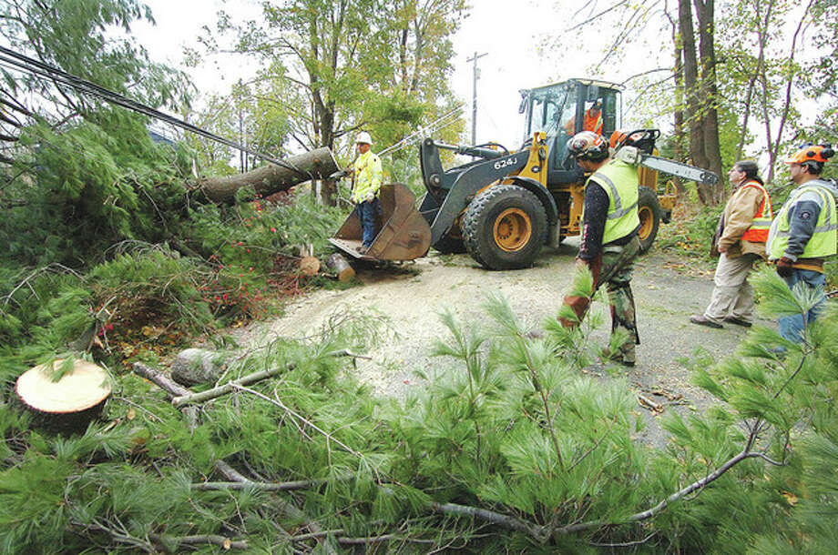 Hour photo / Alex von KleydorffRick Matthews with the Town of Wilton Public Works brings a lineman with Missouri PAL Power closer to the powerlines in the bucket of his loader as town crews and Knapp Tree Service converge on Pine Ridge Road on Thursday to open the only access for residents living beyond the two downed trees to get in or more important get out. / 2012 The Hour Newspapers