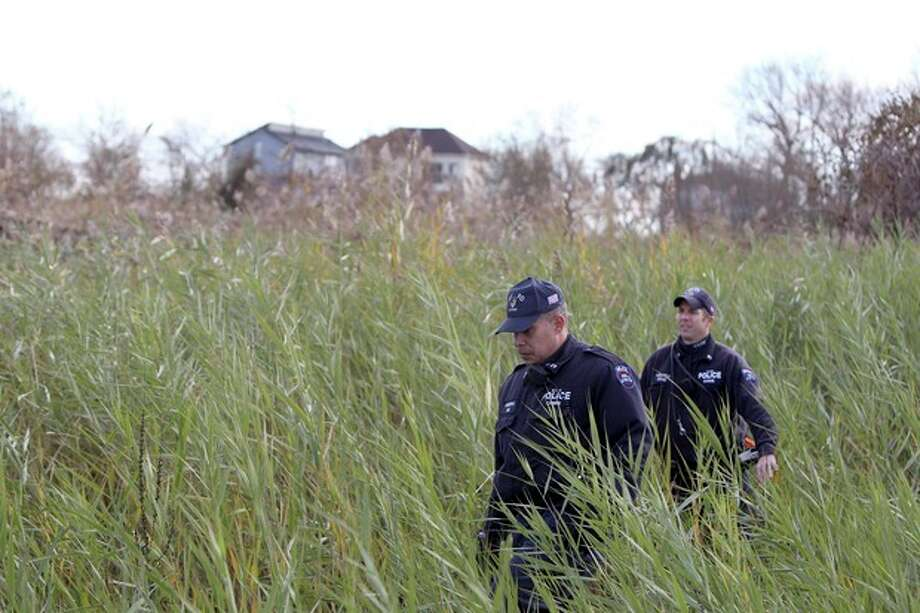 Police officers wearing wet suits leave a site where the body of a 2-year-old child killed during Superstorm Sandy was discovered in Staten Island, New York, Thursday, Nov. 1, 2012. Brandon Moore, 2, and Connor Moore, 4, were swiped into swirling waters as their mother tried to escape her SUV on Monday amid rushing waters that caused the vehicle to stall during Superstorm Sandy. Police said the mother, Glenda Moore, was going to her sister's home in Brooklyn when she tried to flee the vehicle with the boys, only to have the force of the rising water and the relentless cadence of pounding waves rip the boy's small arms from her. (AP Photo/Seth Wenig) / AP
