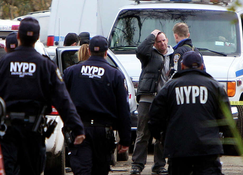 Damian Moore, reacts as he approaches the scene where at least one of his childrens' bodies were discovered in Staten Island, New York, Thursday, Nov. 1, 2012. Brandon Moore, 2, and Connor Moore, 4, were swiped into swirling waters as their mother tried to escape her SUV on Monday amid rushing waters that caused the vehicle to stall during Superstorm Sandy. Police said the mother, Glenda Moore, was going to her sister's home in Brooklyn when she tried to flee the vehicle with the boys, only to have the force of the rising water and the relentless cadence of pounding waves rip the boy's small arms from her. (AP Photo/Seth Wenig) / AP