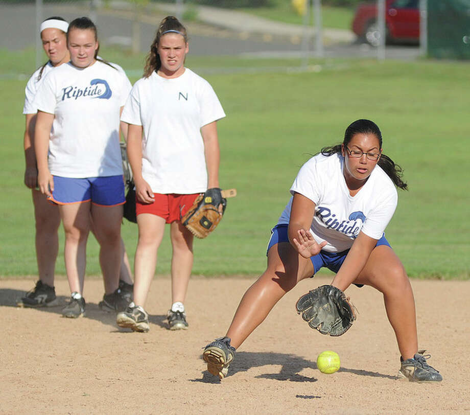 Hour photo/John NashNorwalk Riptide U-16 infielder Tori Rodriguez, right, fields a ground ball under the watchful of eye of teammates during a practice on Monday. The team has received an at-large bid to the Babe Ruth Softball World Series in North Carolina.
