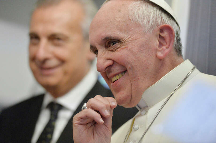 """Pope Francis answers reporters questions during a news conference aboard the papal flight on the journey back from Brazil, Monday, July 29, 2013. Pope Francis reached out to gays on Monday, saying he wouldn't judge priests for their sexual orientation in a remarkably open and wide-ranging news conference as he returned from his first foreign trip. """"If someone is gay and he searches for the Lord and has good will, who am I to judge?"""" Francis asked. His predecessor, Pope Benedict XVI, signed a document in 2005 that said men with deep-rooted homosexual tendencies should not be priests. Francis was much more conciliatory, saying gay clergymen should be forgiven and their sins forgotten. Francis' remarks came Monday during a plane journey back to the Vatican from his first foreign trip in Brazil. (AP Photo/Luca Zennaro, Pool) / ANSA"""