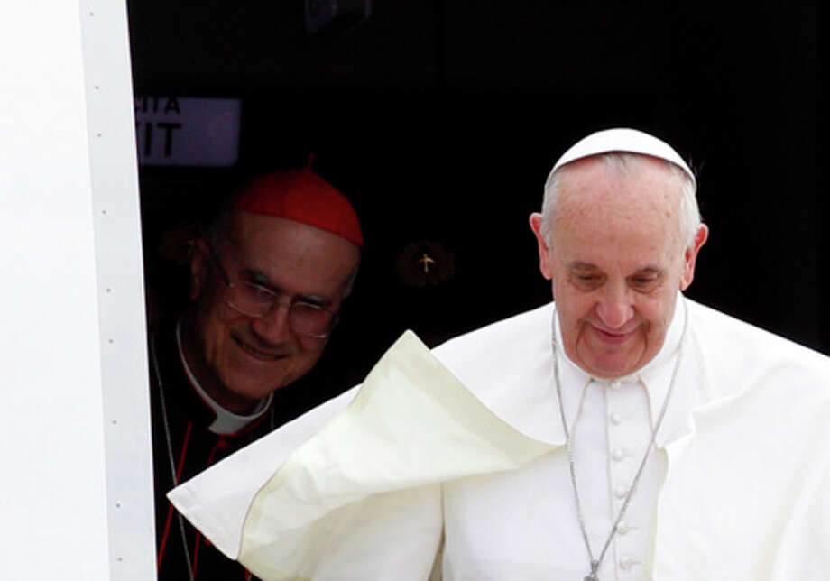 Pope Francis, followed by Vatican Secretary of State Cardinal Tarcisio Bertone, disembarks from the plane after landing from Rio de Janeiro, Brazil, at Ciampino's military airport, on the outskirts of Rome, Monday, July 29, 2013. The pontiff returned after a week in Brazil. (AP Photo/Riccardo De Luca) / AP