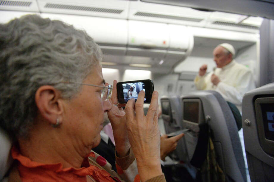 "A journalist takes a photo of Pope Francis speaking during a news conference aboard the papal flight on the journey back from Brazil, Monday, July 29, 2013. Pope Francis reached out to gays on Monday, saying he wouldn't judge priests for their sexual orientation in a remarkably open and wide-ranging news conference as he returned from his first foreign trip. ""If someone is gay and he searches for the Lord and has good will, who am I to judge?"" Francis asked. His predecessor, Pope Benedict XVI, signed a document in 2005 that said men with deep-rooted homosexual tendencies should not be priests. Francis was much more conciliatory, saying gay clergymen should be forgiven and their sins forgotten. Francis' remarks came Monday during a plane journey back to the Vatican from his first foreign trip in Brazil. (AP Photo/Luca Zennaro, Pool) / ANSA"
