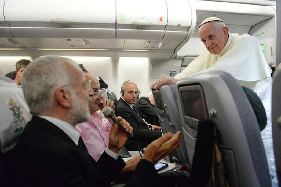 """Pope Francis answers reporters questions during a news conference aboard the papal flight on its way back from Brazil, Monday, July 29, 2013. Pope Francis reached out to gays on Monday, saying he wouldn't judge priests for their sexual orientation in a remarkably open and wide-ranging news conference as he returned from his first foreign trip. """"If someone is gay and he searches for the Lord and has good will, who am I to judge?"""" Francis asked. His predecessor, Pope Benedict XVI, signed a document in 2005 that said men with deep-rooted homosexual tendencies should not be priests. Francis was much more conciliatory, saying gay clergymen should be forgiven and their sins forgotten. Francis' remarks came Monday during a plane journey back to the Vatican from his first foreign trip in Brazil. (AP Photo/Luca Zennaro, Pool) / ANSA"""