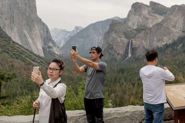 Visitors take pictures of Yosemite Valley in Yosemite National Park, Calif., Saturday, June 11, 2016.