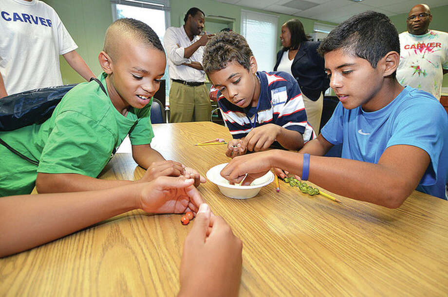 Hour photo/Alex von KleydorffTeam members AJ. Robinson, Angel Torres and Kevin Morataya work on a science problem this week with Dr. Pierre Louis at the Carver Center summer science and math program.