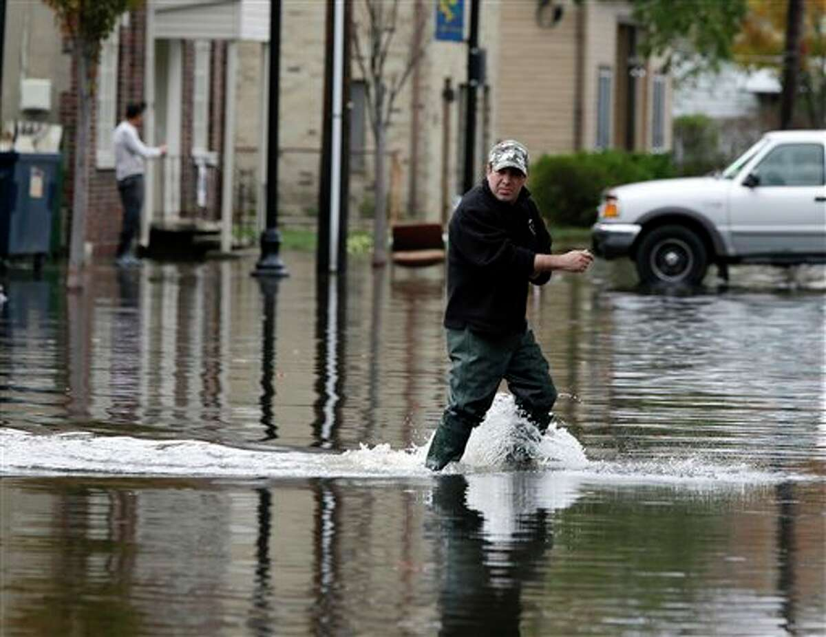 A man crosses a flooded street in the wake of superstorm Sandy on Thursday, Nov. 1, 2012, in Little Ferry, N.J. Surprise coastal surge floods caused by the storm battered Little Ferry, Moonachie and some other towns along the Hackensack River in Bergen County _ all areas unaccustomed to flooding. (AP Photo/Mike Groll)
