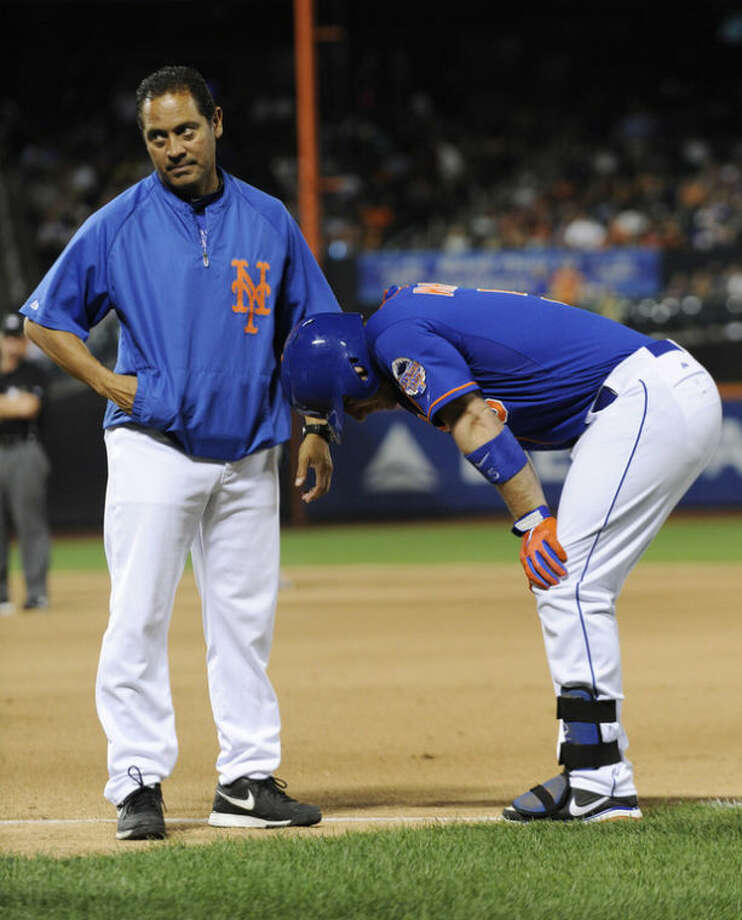 Trainer Ray Ramirez, left, reacts as he talks with New York Mets' David Wright after Wright injured his hamstring during the tenth inning of an interleague baseball game against the Kansas City Royals Friday, Aug. 2, 2013 at Citi Field in New York. (AP Photo/Bill Kostroun)