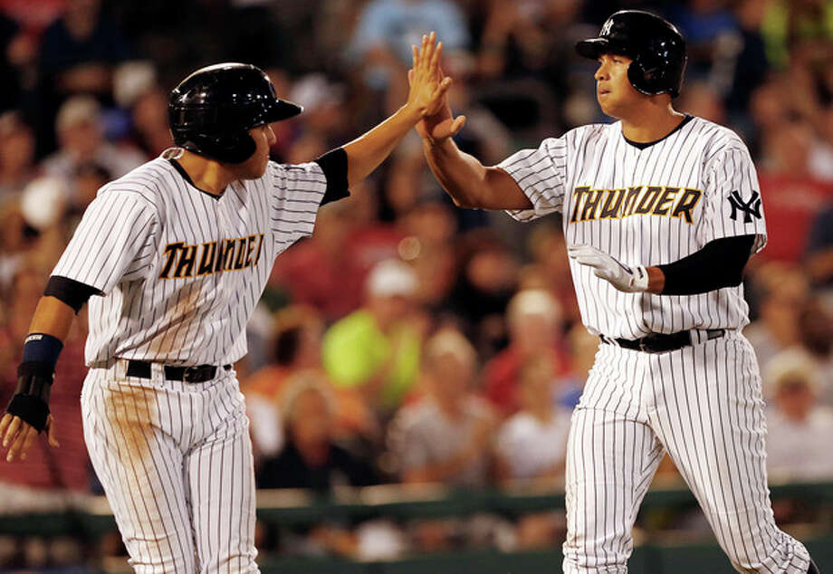 New York Yankees' Alex Rodriguez , right, high-fives Ramon Flores, left, after scoring in the fifth inning of a Class AA baseball game with the Trenton Thunder against the Reading Phillies Saturday, Aug. 3, 2013, in Trenton, N.J. (AP Photo/Rich Schultz) / FR27227 AP