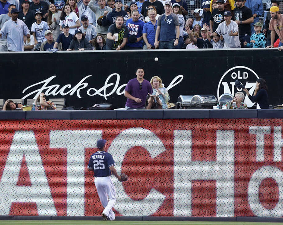 San Diego Padres right fielder Will Venable runs out of room as the home run hit by New York Yankees' Curtis Granderson lands in the stands in the seventh inning of an interleague baseball game in San Diego, Saturday, Aug. 3, 2013. (AP Photo/Lenny Ignelzi) / AP