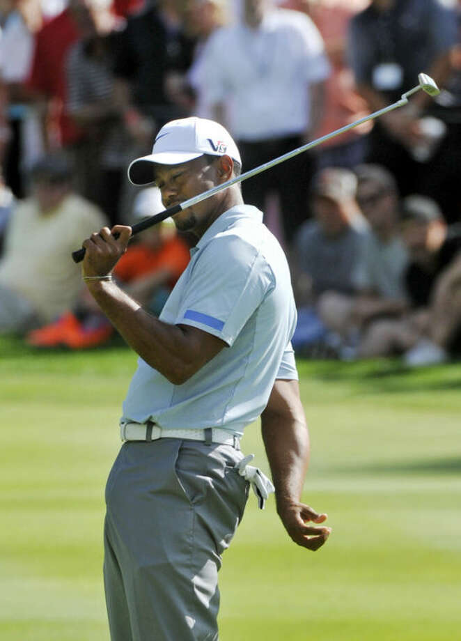 Tiger Woods reacts after missing a putt on the 15th green during the third round of the Bridgestone Invitational golf tournament Saturday, Aug. 3, 2013, at Firestone Country Club in Akron, Ohio. Woods leads the tournament by seven shots at 15-under par. (AP Photo/Phil Long)
