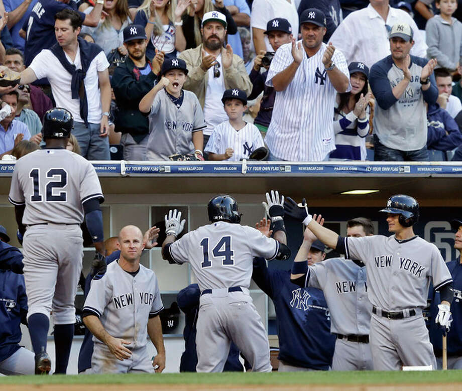New York Yankees' Curtis Granderson is greeted at the dugout after his two-run home run against the San Diego Padres in the seventh inning of an interleague baseball game in San Diego, Saturday, Aug. 3, 2013. (AP Photo/Lenny Ignelzi) / AP