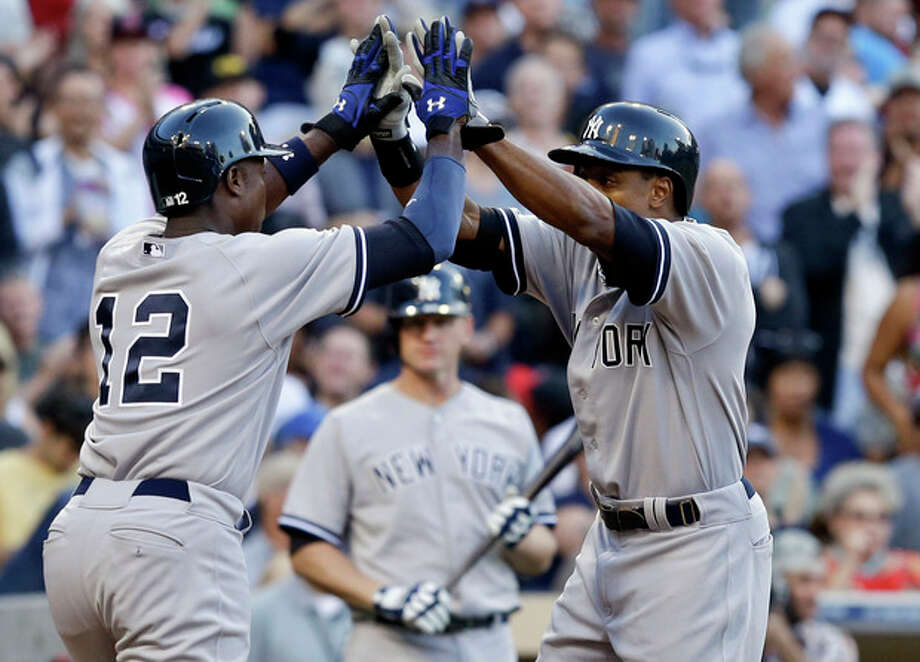 New York Yankees' Curtis Granderson , right, and Alfonso Soriano high five after Granderson's two-run home run against the San Diego Padres in the seventh inning of an interleague baseball game in San Diego, Saturday, Aug. 3, 2013. (AP Photo/Lenny Ignelzi) / AP