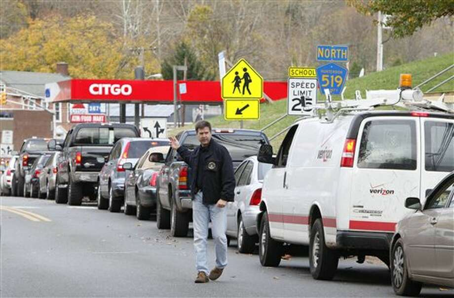 A police officer directs traffic as a line of motorists stretches down Frenchtown Road Thursday morning, Nov. 1, 2012 as customers wait to enter a gas station in Milford Borough, N.J. At 10 a.m. the line exceeded 50 cars and caused congestion at the intersection of Milford-Mt. Pleasant Road. (AP Photo/The Express-Times, Stephen Flood) / The Express-Times