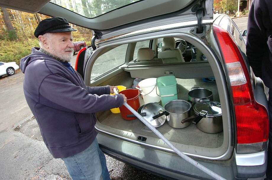 Hour Photo Alex von Kleydorff; Ed Hyde uses a hose supplied from a hydrant for everyones use at Wilton Fire Headquaters to fill pots and buckets in the back of his Volvo wagon, with no power this was his second trip to fill up.