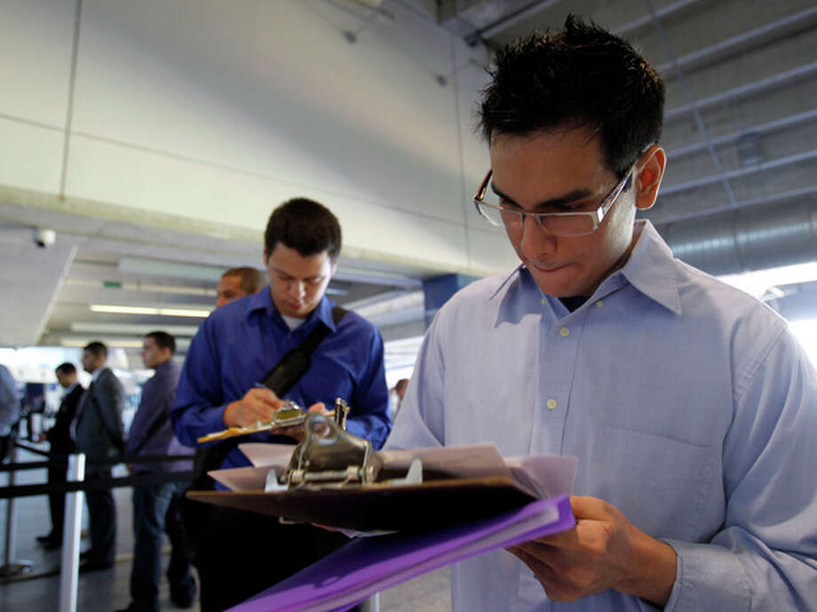 In this Wednesday, Oct. 24, 2012 photo, Fabio Magliano, right, fills out a job application as he stands in line at a job fair in Miami. According to government reports released Friday, Nov. 2, 2012, the U.S. economy added 171,000 jobs in October, and the unemployment rate ticked up to 7.9 percent. (AP Photo/Alan Diaz) / AP