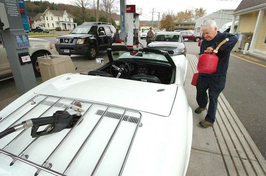 Hour Photo Alex von Kleydorff; At Citgo on Rt 7 in Wilton, Howard Martin places a few gas cans he has filled into his classic 1975 Chevy Corvette. He has also filled the tank because it was built in the 70's he is able to siphon the gas from the cars tank into his generator at home to keep that running power for his house.