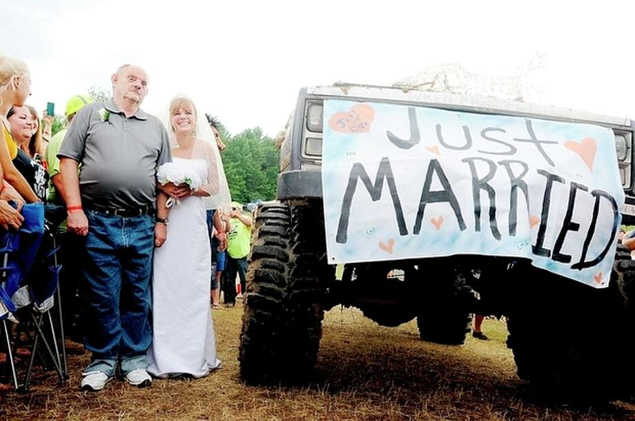 """Lucretia (Blais) Gould of Lewiston, Maine, walks down the aisle with her father, Larry Blais, of Auburn, Maine, during her wedding at the Redneck """"Blank"""" in Hebron, Maine, on Saturday, Aug. 3, 2013. Despite being forced to change its name, the event formerly known as the Redneck Olympic Games continued its tradition Saturday of holding unorthodox competitions like lawn mower races, mud runs and tire burnouts. (AP Photo/Sun Journal, Daryn Slover) / Sun Journal"""