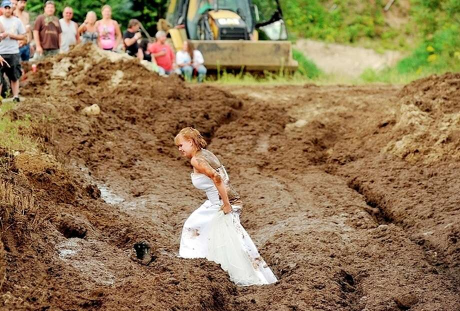 "Lucretia (Blais) Gould walks through the mud run pit in her wedding dress after getting married to Jeff Gould at the Redneck ""Blank"" in Hebron, Maine, on Saturday, Aug. 3, 2013. Despite being forced to change its name, the event formerly known as the Redneck Olympic Games continued its tradition Saturday of holding unorthodox competitions like lawn mower races, mud runs and tire burnouts. (AP Photo/Sun Journal, Daryn Slover) / Sun Journal"