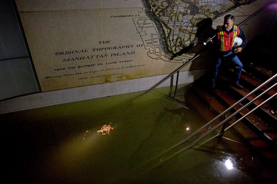 Joseph Leader, Metropolitan Tranportation Authority Vice President and Chief Maintenance Officer, shines a flashlight on standing water inside the South Ferry 1 train station in New York, N.Y., Wednesday, Oct. 31, 2012, in the wake of superstorm Sandy. The floodwaters that poured into New York's deepest subway tunnels may pose the biggest obstacle to the city's recovery from the worst natural disaster in the transit system's 108-year history. (AP Photo/Craig Ruttle) / FR61802 AP
