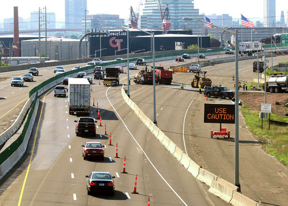 In this July 27, 2013 photo, traffic moves along southbound Interstate 95 in New Haven, Conn., after the traffic pattern was diverted from the old Pearl Harbor Memorial Bridge approach, right, to the new span. Thirteen years into the $2 billion, 16-year reconstruction of the bridge and highway project, construction is under budget and ahead of schedule by a couple of months, the state Department of Transportation said. (AP Photo/New Haven Register, Arnold Gold) / New Haven Register