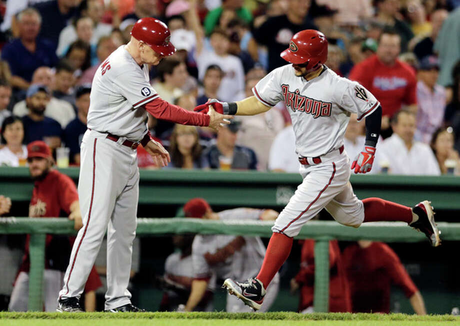 Arizona Diamondbacks' Cody Ross, right, is congratulated by third base coach Matt Williams as he rounds the bases after a solo home run in the seventh inning of a baseball game against the Boston Red Sox at Fenway Park, Friday, Aug. 2, 2013, in Boston. (AP Photo/Charles Krupa) / AP