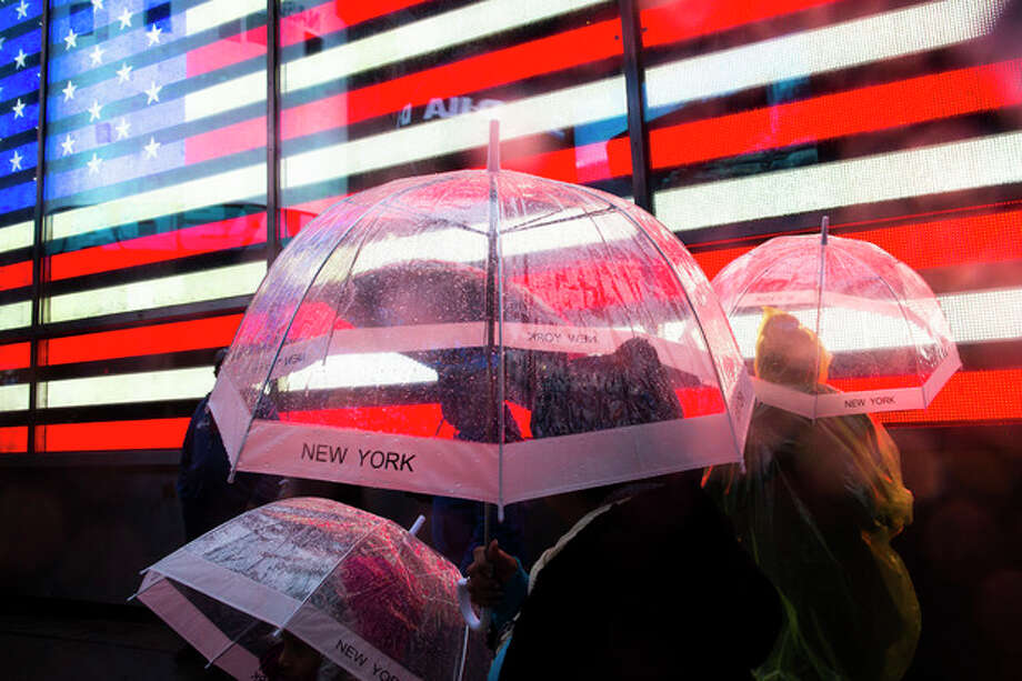 Pedestrians huddle under their umbrellas in Times Square, Monday, Oct. 29, 2012, in New York. Hurricane Sandy continued on its path Monday, as the storm forced the shutdown of mass transit, schools and financial markets, sending coastal residents fleeing, and threatening a dangerous mix of high winds and soaking rain. (AP Photo/ John Minchillo) / FR170537 AP
