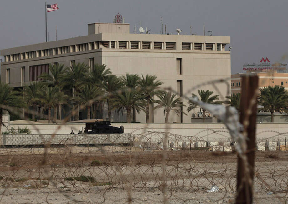 A Bahraini armored personnel vehicle and personnel reinforce U.S. Embassy security just outside of a gate to the building, surrounded in barbed wire, in Manama, Bahrain, on Sunday, Aug. 4, 2013. Security forces close access roads, put up extra blast walls and beef up patrols near some of the 21 U.S. diplomatic missions in the Muslim world that Washington ordered closed for the weekend over a ``significant threat'' of an al-Qaida attack. (AP Photo/Hasan Jamali) / AP
