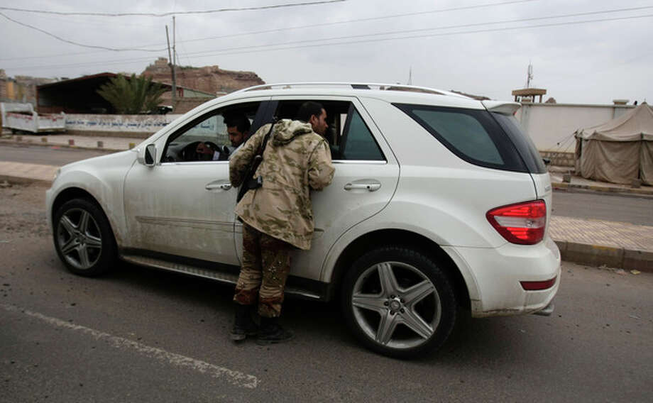 A Yemeni soldier inspects a car at a checkpoint on a street leading to the U.S. embassy in Sanaa, Yemen, Sunday, Aug. 4, 2013. Security forces close access roads, put up extra blast walls and beef up patrols near some of the 21 U.S. diplomatic missions in the Muslim world that Washington ordered closed for the weekend over a ``significant threat'' of an al-Qaida attack. (AP Photo/Hani Mohammed) / AP