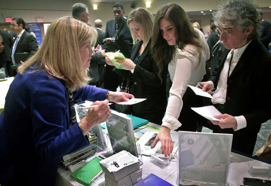 In this Wednesday, Oct. 24, 2012, photo, Patricia Mazza, left, meets job seekers, including recent college grads Ashley Deyo, 22, second from left, and Chyna Dama, 23, second from right, during a National Career Fairs' job fair, in New York. Weekly applications for U.S. unemployment benefits dropped 9,000 last week to a seasonally adjusted 363,000, the Labor Department said Thursday, Nov. 1, 2012. The level is consistent with modest hiring. (AP Photo/Bebeto Matthews) / AP