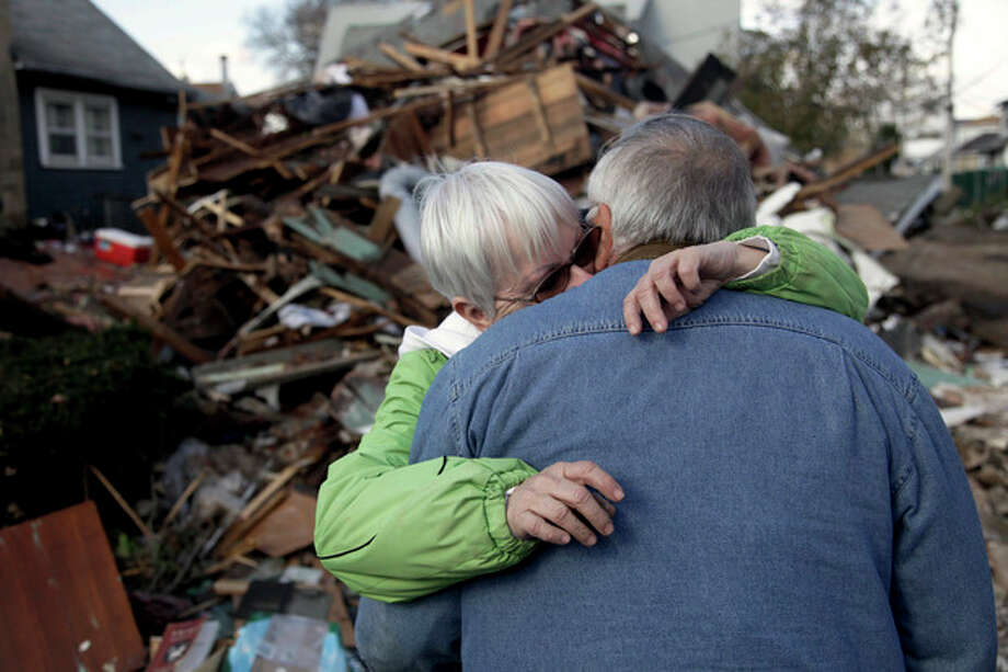 Sheila and Dominic Traina hug in front of their home which was demolished during Superstorm Sandy in Staten Island, N.Y., Friday, Nov. 2, 2012. Mayor Michael Bloomberg has come under fire for pressing ahead with the New York City Marathon. Some New Yorkers say holding the 26.2-mile race would be insensitive and divert police and other important resources when many are still suffering from Superstorm Sandy. The course runs from the Verrazano-Narrows Bridge on hard-hit Staten Island to Central Park, sending runners through all five boroughs. The course will not be changed, since there was little damage along the route. (AP Photo/Seth Wenig) / AP