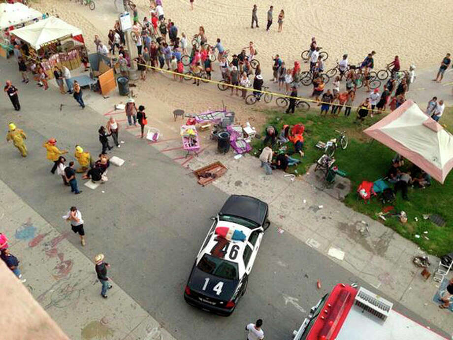 Pedestrians gather as police and fire officials respond after a car drove through a packed afternoon crowd along the Venice Beach boardwalk in Los Angeles, Saturday, Aug. 3, 2013. At least a dozen people were injured, two of them critically, according to police. (AP Photo/Maarten Smitskamp) / AP