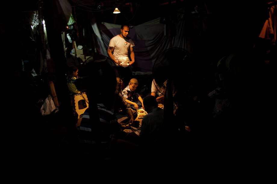 Supporters of Egypt's ousted President Mohammed Morsi break their fast during a protest near Cairo University in Giza, Egypt, Sunday, Aug. 4, 2013. (AP Photo/Manu Brabo) / AP