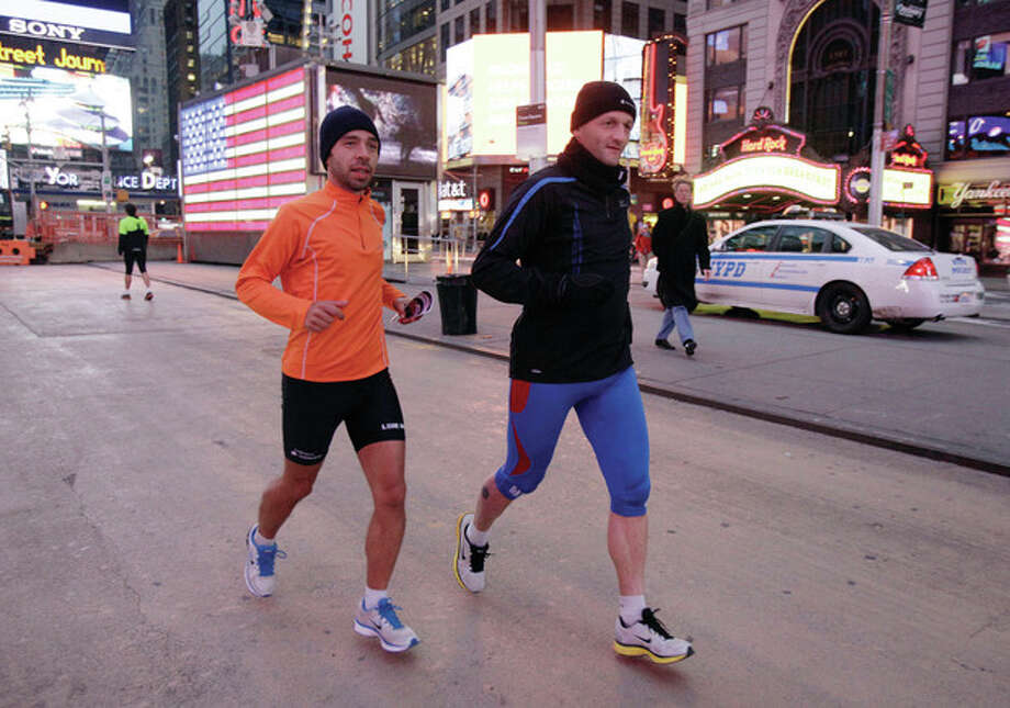 AP photoRicardo Burnia, left, and Simon Capaccioni, from Perugia, Italy, train for the New York City Marathon in New York's Times Square on Friday prior to the announcement that the marathon would be canceled. / AP