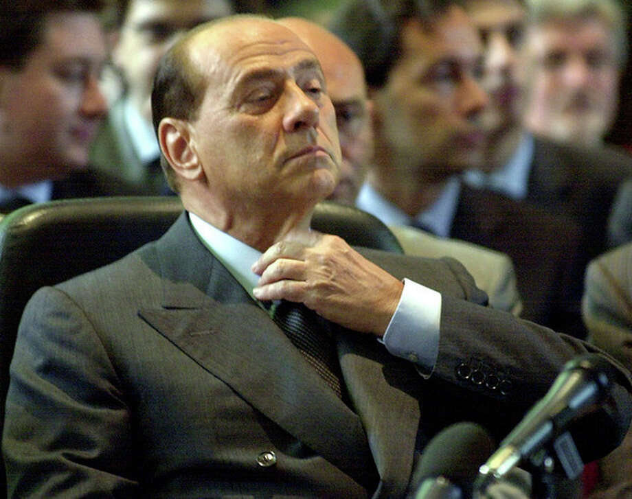 FILE - In this file photo taken June 17, 2003 Silvio Berlusconi adjusts his tie before addressing the Law court in Milan, Italy. Italy's top court confirmed Thursday, Aug. 1, 2013 Berlusconi tax fraud conviction, and ordered the review of a political ban contained in the sentence that was appealed by the Italian media Mogul. (AP Photo/Antonio Calanni, file) / AP
