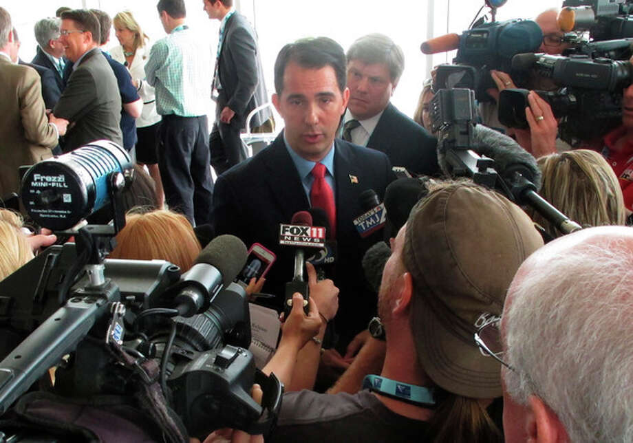 Wisconsin Gov. Scott Walker draws the biggest crowd of reporters following a news conference on the opening day of the National Governors Association meeting on Friday, Aug. 2, 2013, in Milwaukee, Wis. (AP Photo/Scott Bauer) / AP