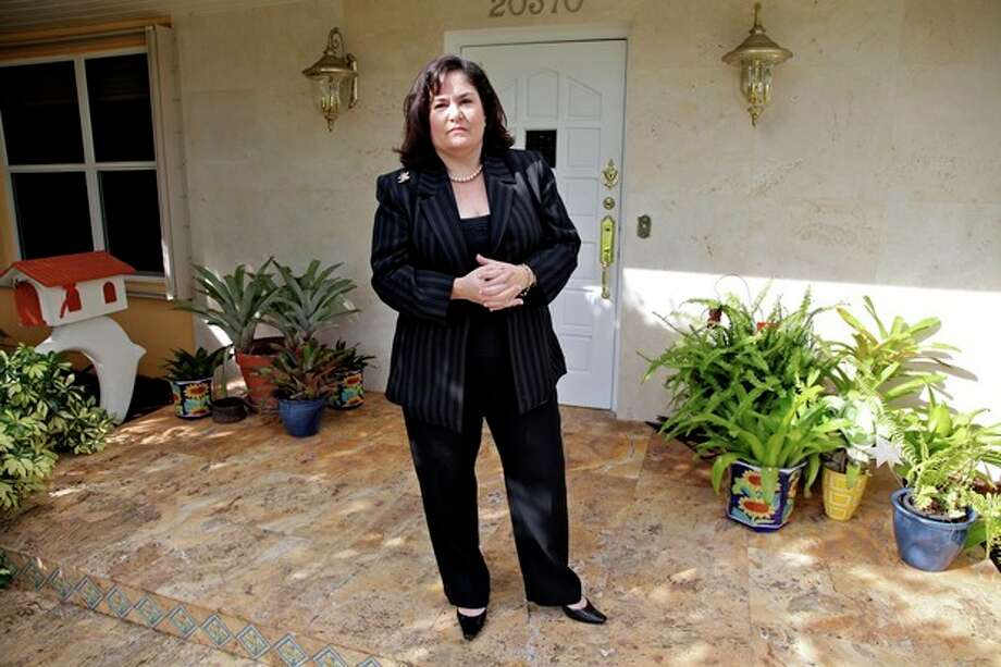 In this Oct. 23, 2012, photo, Hilda Mitrani, 51, of North Miami Beach, Fla., poses by her home in Miami. Mitrani has a marketing consulting company and is among many feeling squeezed by a painfully sluggish economic rebound. Unemployment remains high at 7.8 percent. Average pay trails inflation. And the economy is growing too slowly to accelerate hiring. Polls consistently find that the economy is the top concern of voters, and Romney tends to get an edge over Obama when people are asked who might do better with it. Whether that truly drives how Americans vote is a crucial question for Election Day. (AP Photo/Robert Ray) / AP
