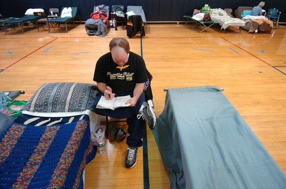 Hour Photo Alex von Kleydorff; Christopher Backiel stays busy doing crosswords while staying at the emergency shelter at Brien Mcmahon High School on Friday. Guest numbers have dropped off somewhat but are expected to climb again due to colder temperatures at the citys shelter