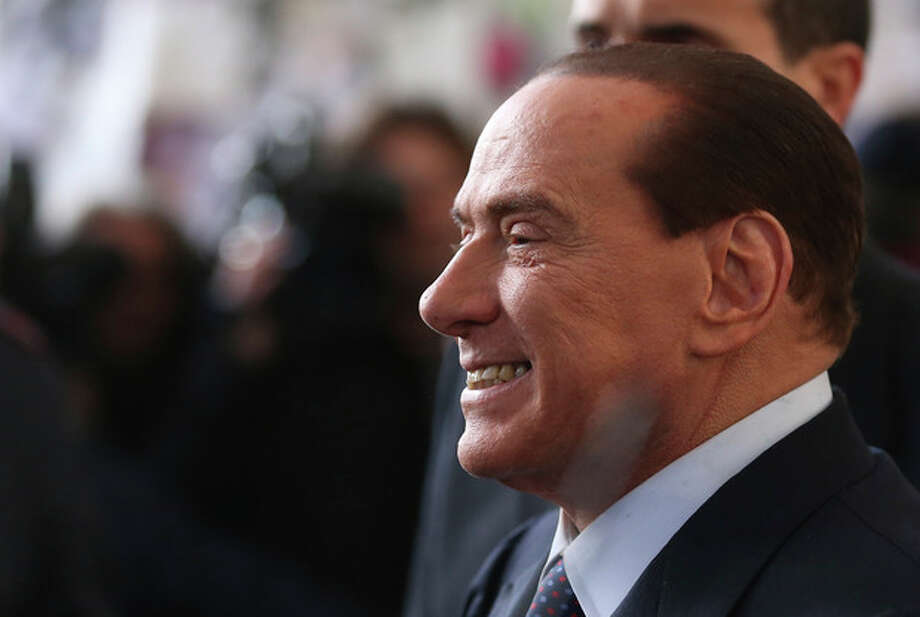 FILE - In this file photo taken Dec. 29, 2012 Silvio Berlusconi smiles as he arrives at Milan's central train station, Italy. Italy's top court confirmed Thursday, Aug. 1, 2013 Berlusconi tax fraud conviction, and ordered the review of a political ban contained in the sentence that was appealed by the Italian media Mogul. (AP Photo/Luca Bruno, file) / AP