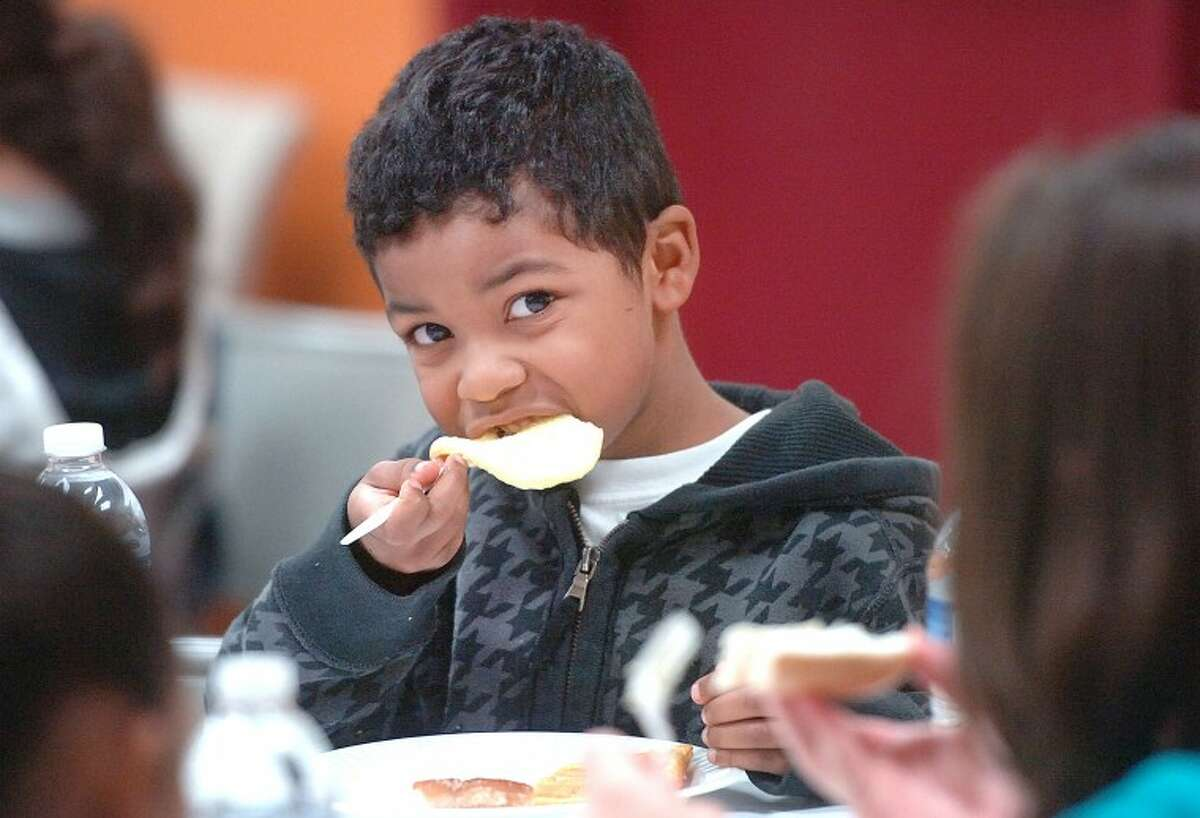 Hour Photo Alex von Kleydorff; 6yr old Michael Clarke trys to get the whole pancake in at breakfast with his family at NEON on Friday morning. Meals were prepared and served with help from GE Capitol volunteers that included pancakes, waffles, bacon, muffins and coffee and juice.