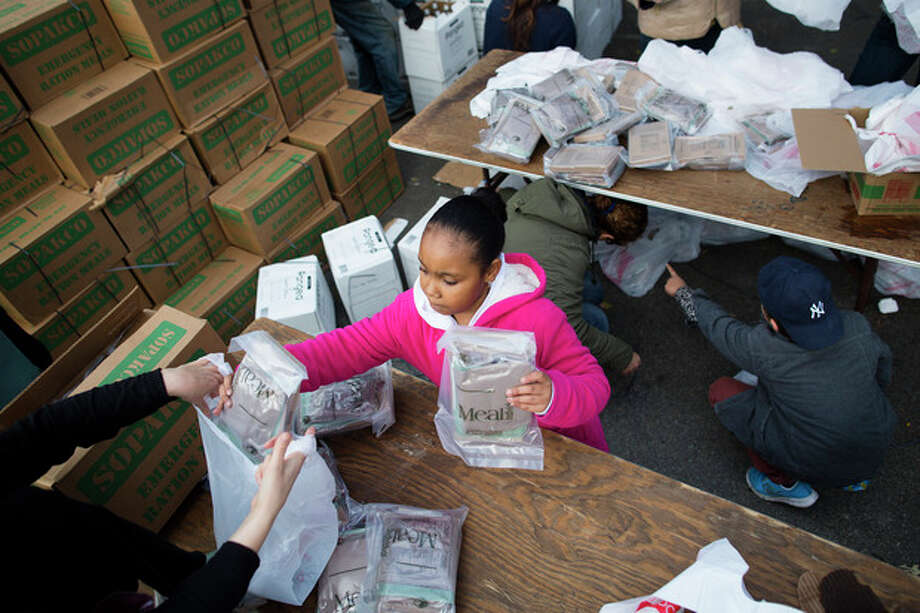 9-year-old Sidney, no last name available, helps bag Meals-Ready-to-Eat (MREs) for distribution to the residents of the Lower East Side who remain without power due to Superstorm Sandy, Friday, Nov. 2, 2012, in New York. In Manhattan, where 226,000 buildings, homes and business remain without power, Consolidated Edison says they should have service restored by Saturday. (AP Photo/ John Minchillo) / FR170537 AP