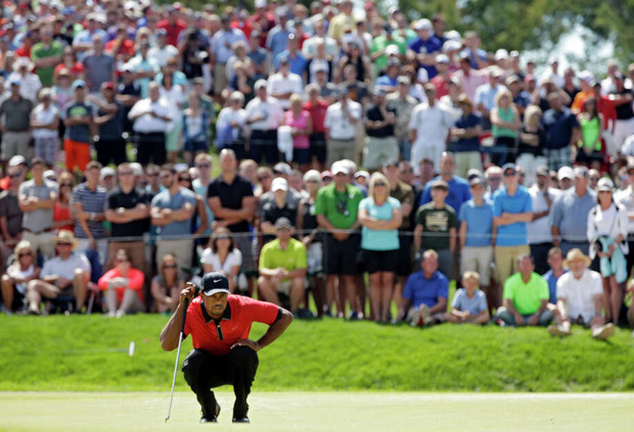 Tiger Woods looks over his putt on the seventh hole during the final round of the Bridgestone Invitational golf tournament Sunday, Aug. 4, 2013 at Firestone Country Club in Akron, Ohio. (AP Photo/Mark Duncan) / AP